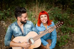 Jeunes couples ayant l'amusement avec la guitare dans le parc Images stock