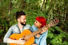 Jeunes couples ayant l'amusement avec la guitare dans le parc Photographie stock libre de droits