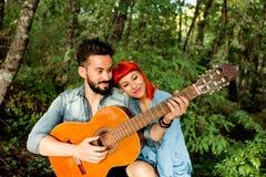 Jeunes couples ayant l'amusement avec la guitare dans le parc Photos stock