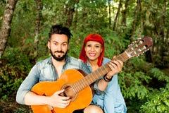 Jeunes couples ayant l'amusement avec la guitare dans le parc Photos libres de droits