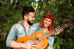 Jeunes couples ayant l'amusement avec la guitare dans le parc Photographie stock