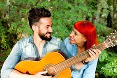 Jeunes couples ayant l'amusement avec la guitare dans le parc Photo libre de droits