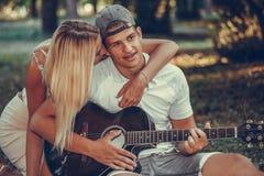 Jeunes couples ayant l'amusement avec la guitare pendant le pique-nique dans le parc images stock
