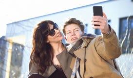 Jeunes couples ayant l'amusement avec le téléphone portable Images libres de droits