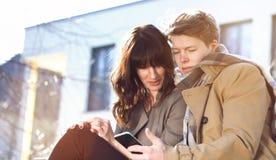 Jeunes couples ayant l'amusement avec le téléphone portable Image libre de droits