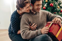 Jeunes couples ayant l'amusement célébrant Noël avec des cadeaux image libre de droits