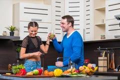 Jeunes couples ayant l'amusement dans la cuisine Photos libres de droits