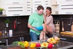 Jeunes couples ayant l'amusement dans la cuisine Image libre de droits