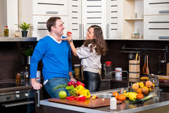 Jeunes couples ayant l'amusement dans la cuisine Photographie stock