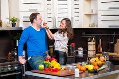 Jeunes couples ayant l'amusement dans la cuisine Photo stock