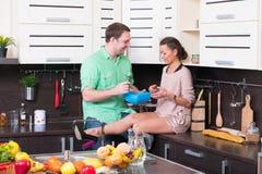 Jeunes couples ayant l'amusement dans la cuisine Photos stock