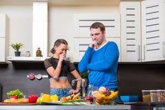 Jeunes couples ayant l'amusement dans la cuisine Photographie stock libre de droits