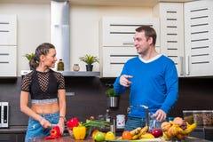 Jeunes couples ayant l'amusement dans la cuisine Images libres de droits