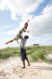 Jeunes couples ayant l'amusement en dunes par Beach Photographie stock libre de droits