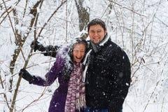 Jeunes couples ayant l'amusement en stationnement de l'hiver photographie stock libre de droits