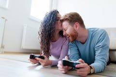 Jeunes couples ayant l'amusement jouant des jeux vidéo Photo stock