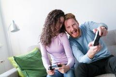 Jeunes couples ayant l'amusement jouant des jeux vidéo Photos stock