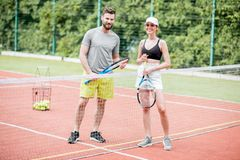 Jeunes couples ayant l'amusement se tenant sur le court de tennis Photo libre de droits