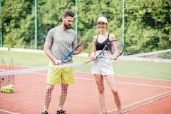 Jeunes couples ayant l'amusement se tenant sur le court de tennis Images stock