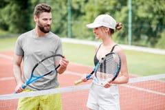 Jeunes couples ayant l'amusement se tenant sur le court de tennis Image libre de droits