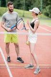 Jeunes couples ayant l'amusement se tenant sur le court de tennis Photos libres de droits
