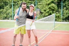 Jeunes couples ayant l'amusement se tenant sur le court de tennis Images libres de droits