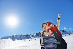 Jeunes couples ayant l'amusement sur la neige Homme heureux à la montagne donnant le tour de ferroutage à son amie de sourire Image stock