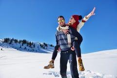 Jeunes couples ayant l'amusement sur la neige Homme heureux à la montagne donnant le tour de ferroutage à son amie de sourire Photographie stock