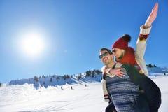 Jeunes couples ayant l'amusement sur la neige Homme heureux à la montagne donnant le tour de ferroutage à son amie de sourire Images stock