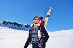 Jeunes couples ayant l'amusement sur la neige Homme heureux à la montagne donnant le tour de ferroutage à son amie de sourire Images libres de droits