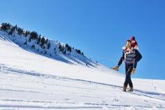 Jeunes couples ayant l'amusement sur la neige Homme heureux à la montagne donnant le tour de ferroutage à son amie de sourire Photo stock