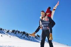 Jeunes couples ayant l'amusement sur la neige Homme heureux à la montagne donnant le tour de ferroutage à son amie de sourire Photos libres de droits
