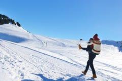 Jeunes couples ayant l'amusement sur la neige Homme heureux à la montagne donnant le tour de ferroutage à son amie de sourire Image libre de droits