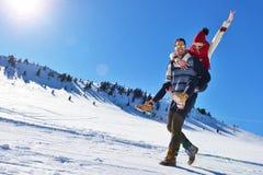 Jeunes couples ayant l'amusement sur la neige Homme heureux à la montagne donnant le tour de ferroutage à son amie de sourire Photo libre de droits