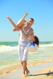 Jeunes couples ayant l'amusement sur la plage Photo stock