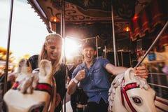 Jeunes couples ayant l'amusement sur le carrousel Photographie stock libre de droits