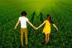 Jeunes couples ayant l'amusement sur le champ vert au printemps ou le résumé Image stock