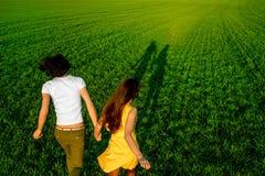 Jeunes couples ayant l'amusement sur le champ vert au printemps ou le résumé Photographie stock libre de droits