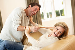 Jeunes couples ayant l'amusement sur le sofa Photo libre de droits