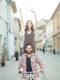 Jeunes couples ayant l'amusement sur le vélo Photo stock