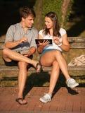 Jeunes couples ayant l'amusement sur un banc dans le parc tout en socialisant l'ove Photo stock