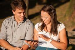 Jeunes couples ayant l'amusement sur un banc dans le parc tout en socialisant l'ove Image stock