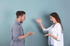 Jeunes couples ayant l'argument sur le fond de couleur photos libres de droits