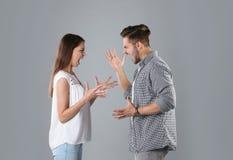 Jeunes couples ayant l'argument sur le fond gris photographie stock