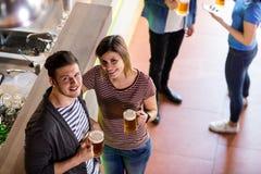 Jeunes couples ayant la bière par le compteur Image libre de droits