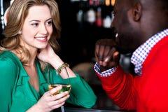 Jeunes couples ayant la conversation dans la barre Image libre de droits
