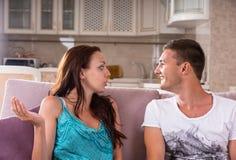 Jeunes couples ayant la conversation sur le sofa à la maison Photos stock