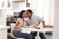 Jeunes couples ayant la séance romantique de repas à la table dans la cuisine, foyer sélectif images stock