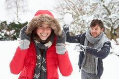 Jeunes couples ayant le combat de boule de neige photos libres de droits