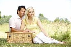 Jeunes couples ayant le pique-nique dans la campagne Photo stock
